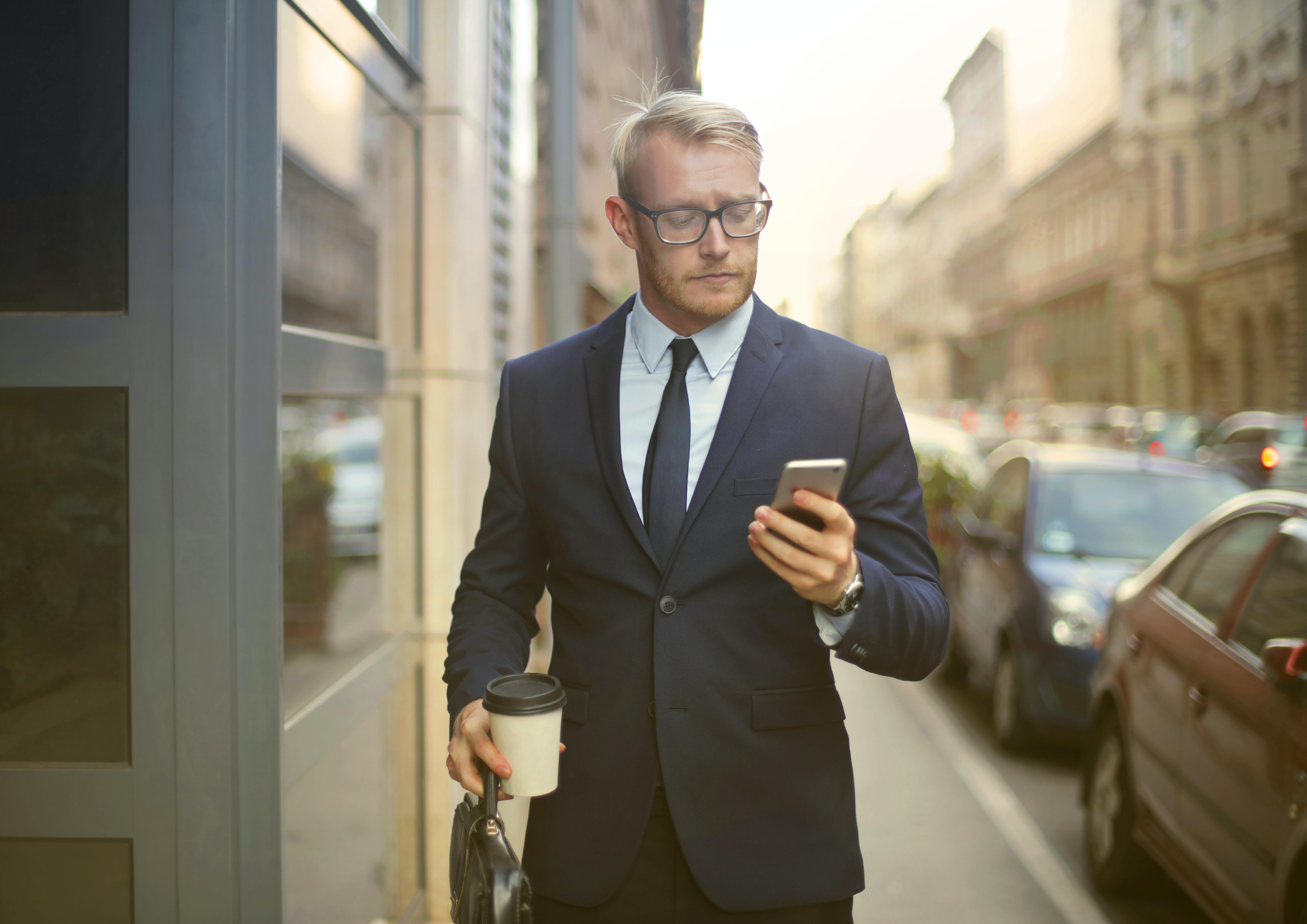 Man on busy street with mobile phone